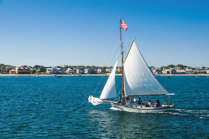 "The 31 foot Friendship Sloop ""Endeavor"",  sailing off the coast of Nantucket,  provides excursion sailings to a group of visitors to this tranquil island"